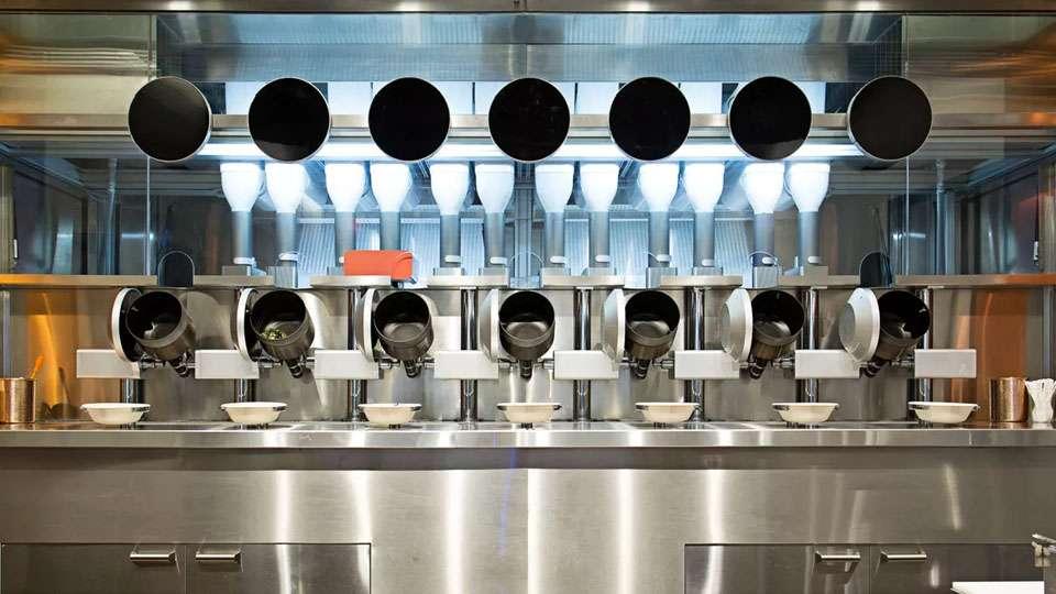 Los robots de Spyce dispensas ingredientes en una línea de ollas giratorias y los cocina mediante inducción electromagnética